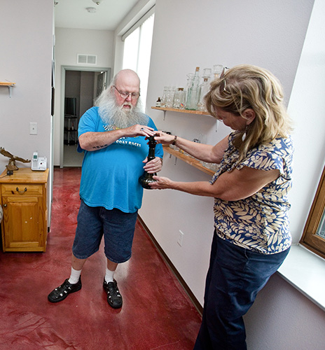 Jeff, an Itasca County resident and affordable housing advocate, shows Audrey Moen a piece in his glass vase collection.